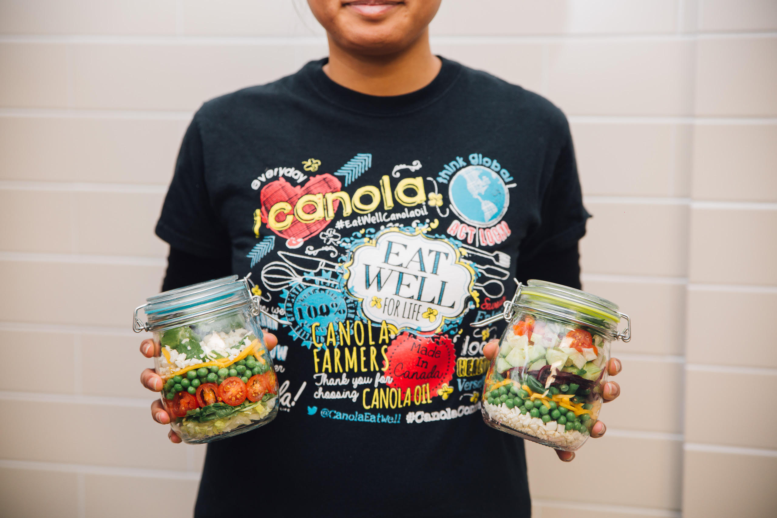 Handmade meal prep jars are held at a Canola Eat Well workshop